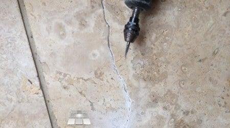 Diamond burr opeining crack in Travertine floor ready for repair